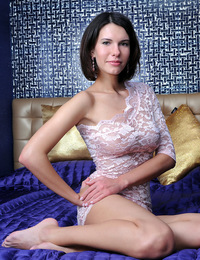 Not wearing any panties at all, Suzanna naughtily poses on top of the bed with her lace dress partly pulled up to show off her sweet, shaven labia. -